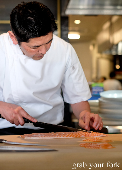Chef Ryuichi Yoshii slicing salmon sashimi at Fujisaki by Lotus at Barangaroo in Sydney