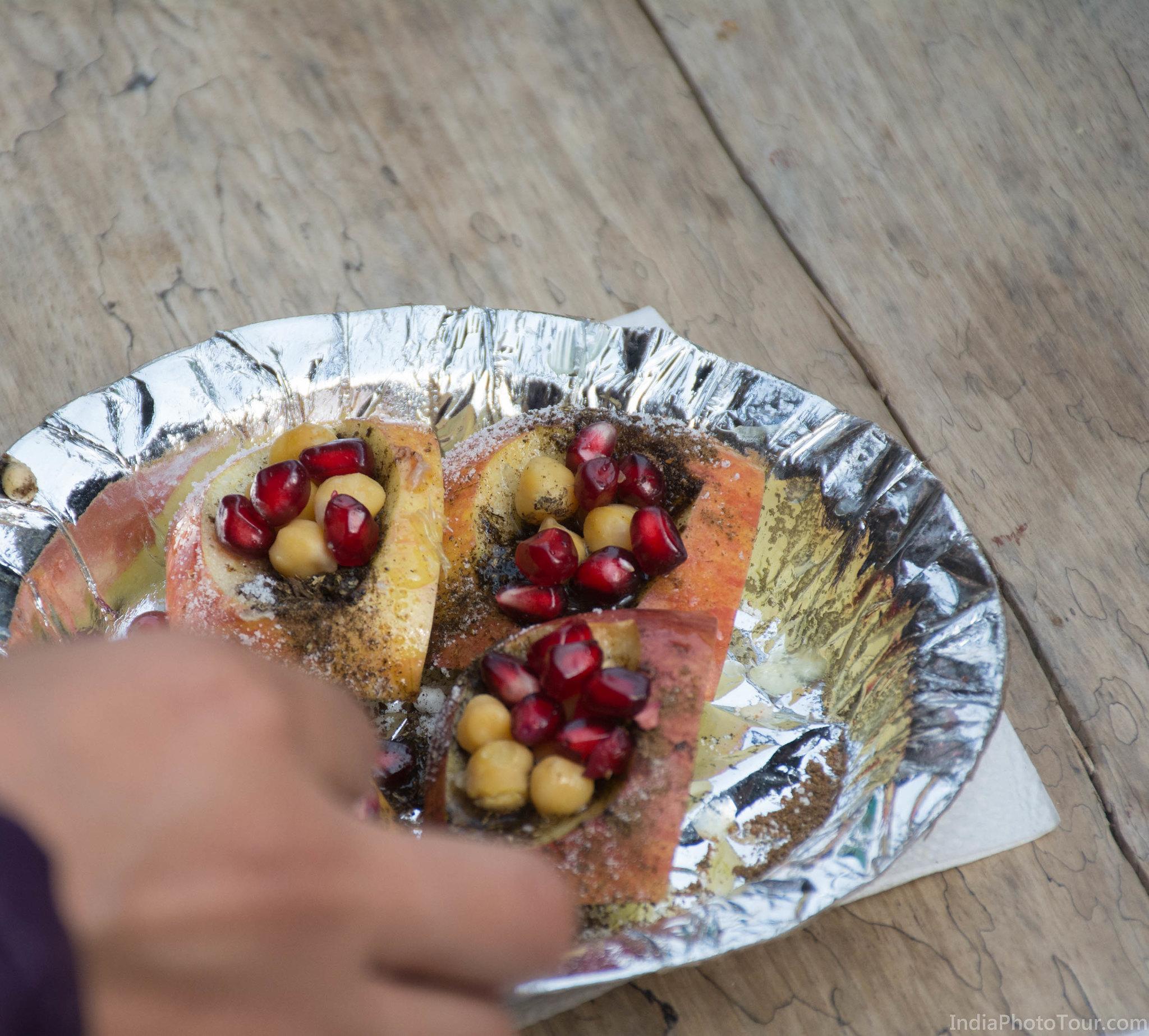 Close up shot of Kulia Chaat made with apples, powdered sugar, chaat masala chick peas, pomegranate and lemon juice