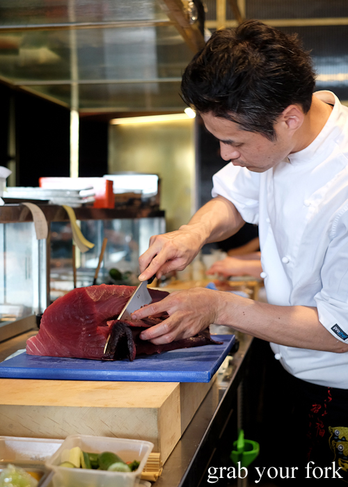 Sushi chef slicing tuna at Fujisaki by Lotus at Barangaroo in Sydney