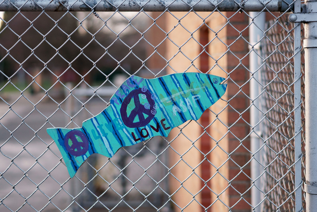 A painted wooden fish on the chain link fence at Irvington School in the Irvington neighborhood of Portland, Oregon