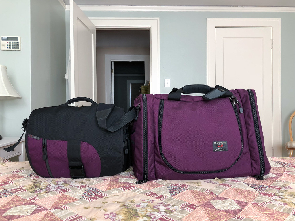 A side-by-side view of the Tom Bihn ID laptop bag and Tom Bihn Aeronaut 45 travel bag, both in aubergine