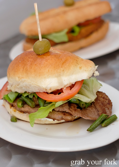 Chivito steak sandwich with beans at Uruguayan bakery cafe Confiteria Lion D'Or in Carramar