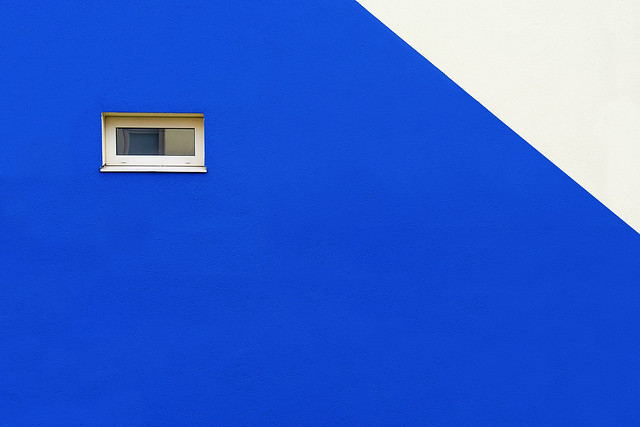 Little window in a blue and white wall