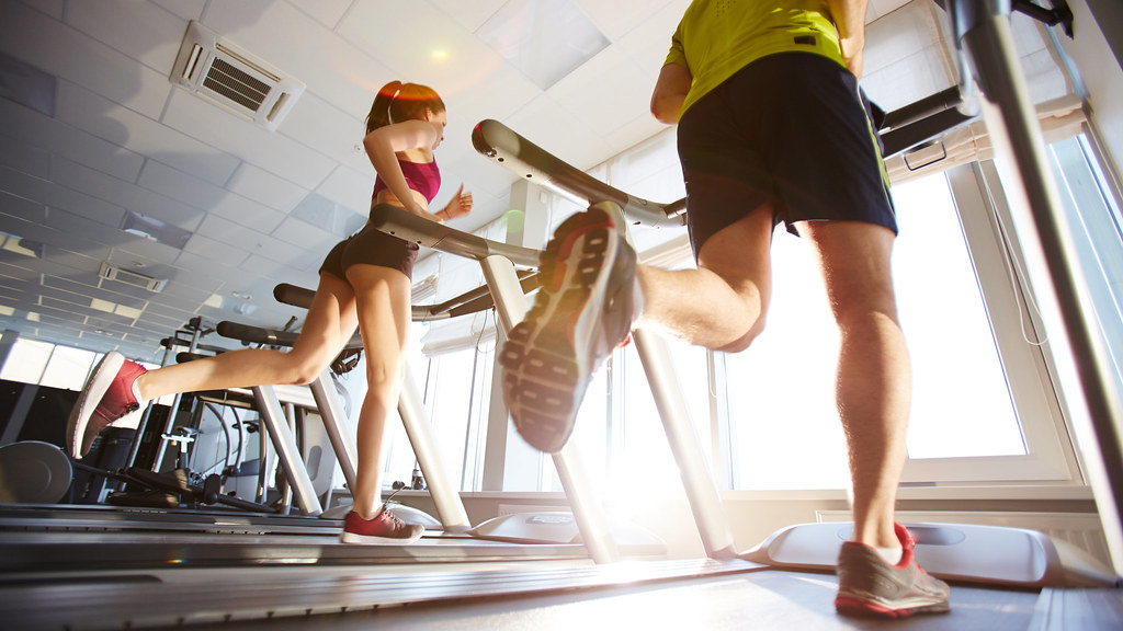 Two people running on treadmills (image iStock 579747000)