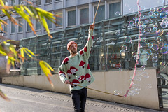 Street performer creating many soap bubbles