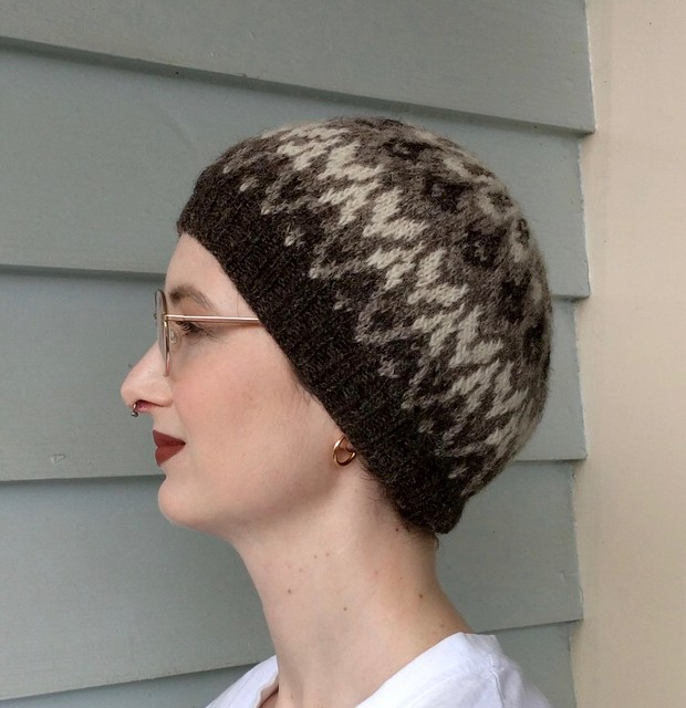 Woman's head in front of weatherboard house. She wears a handknit, colourwork hat in natural shades of brown and white.