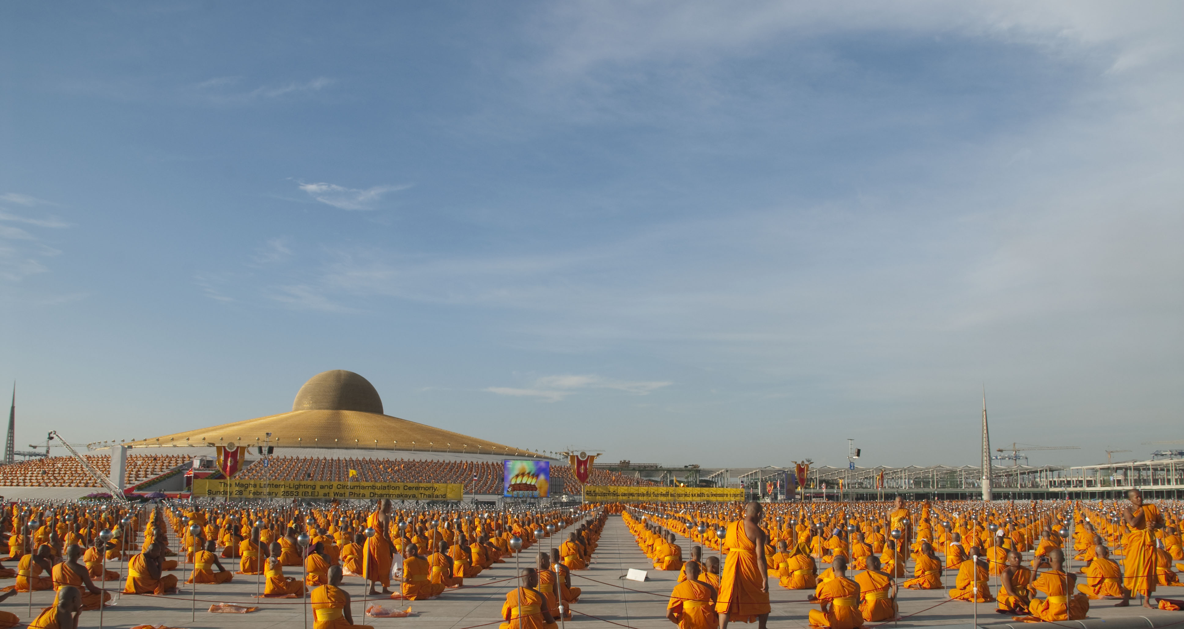 Monks and guests from over 40 countries joyously attend the Makha Bucha Day ceremony at Wat Phra Dhammakaya in Thailand, offering alms to 3,000 monks and lighting 100,000 lanterns in