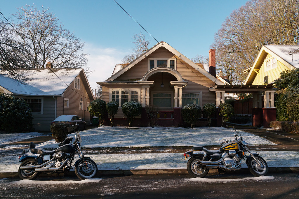 Two motorcyles are parked in front of a house dusted with snow in the Irvington neighborhood of Portland, Oregon