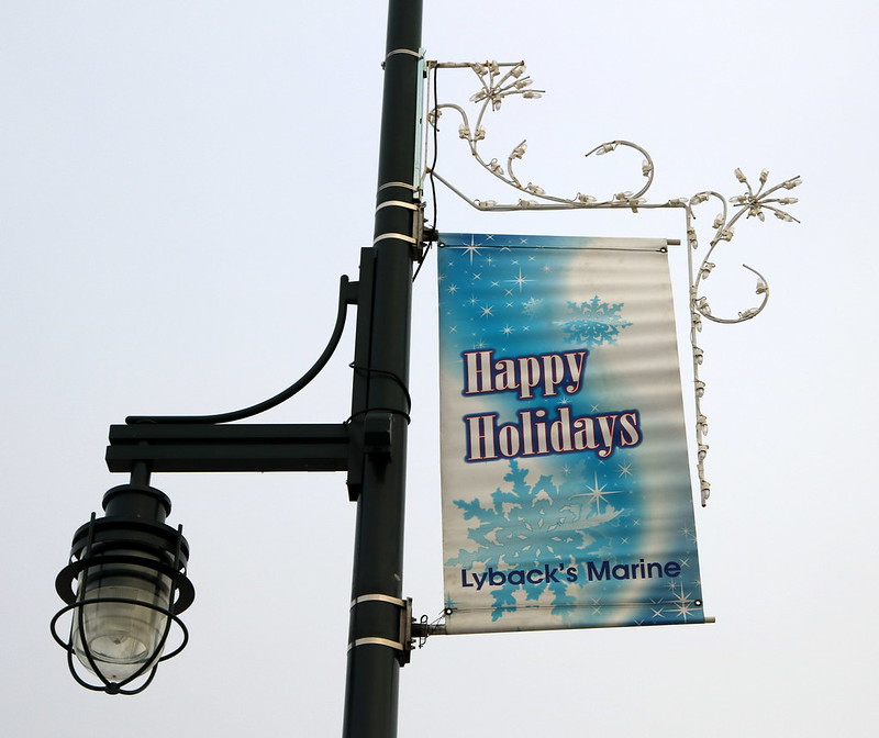 lamppost with a Seasons Greetings banner, with white swoops and star shapes above