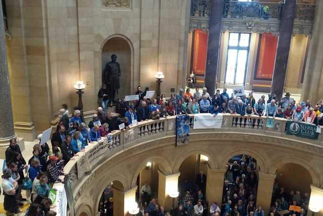 looking down at the rotunda from the third floor, with lots of people holding signs on the first and second floors
