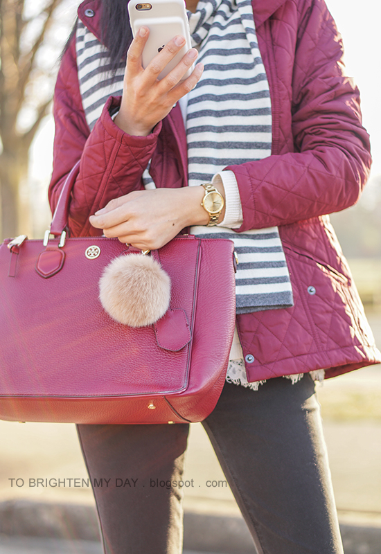 gray and white striped scarf, red quilted jacket, gold watch, purple red tote with fur pom keychain, white sweater with lace hem, black jeans
