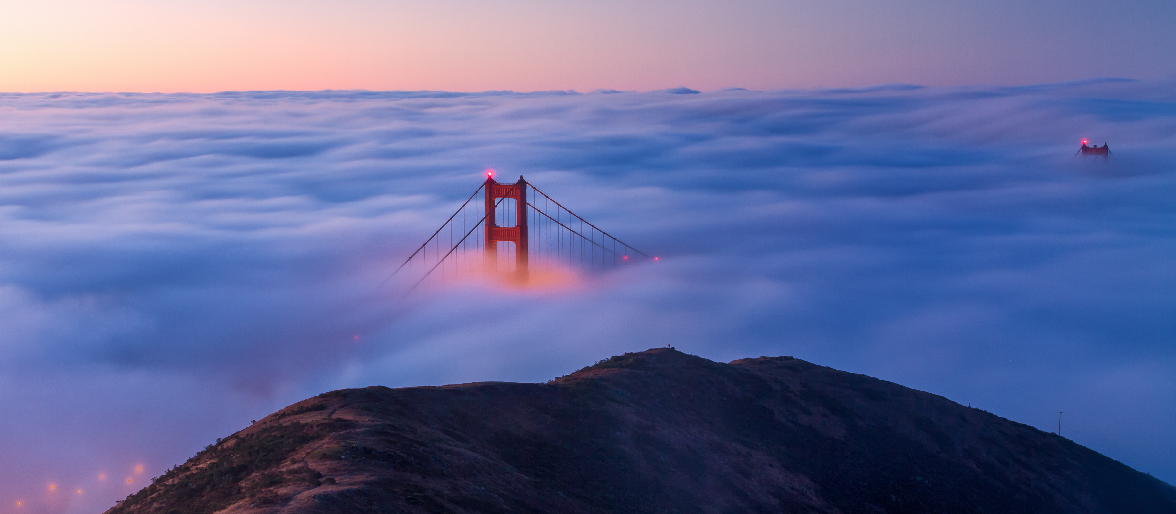A view of the Golden Gate Bridge from the Marin Headlands on a foggy morning at sunrise.