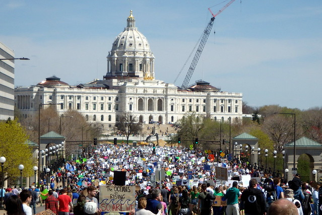 closer in view of the capitol with a crane on the right side, a sea of people in front, lots of neon green signs visible