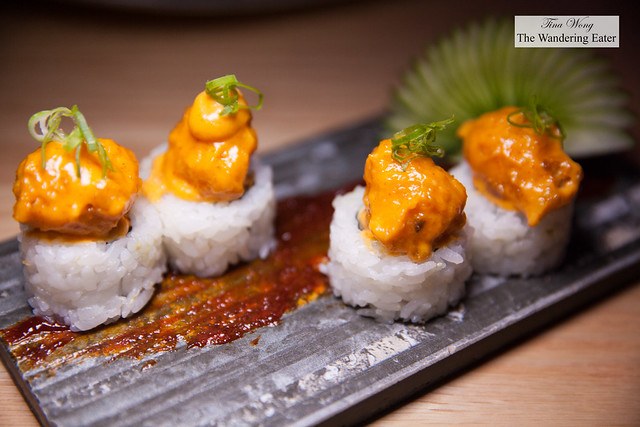 Vegetarian maki roll topped with fried vegetable and spicy sauce