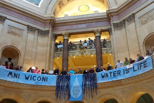 looking up at the second level of the rotunda, with a long Mni Wiconi Water Is Life banner across the image