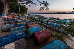 Oil drums and longtail boats: sunset at the boat jetty on the Chindwin River - Monywa, Myanmar