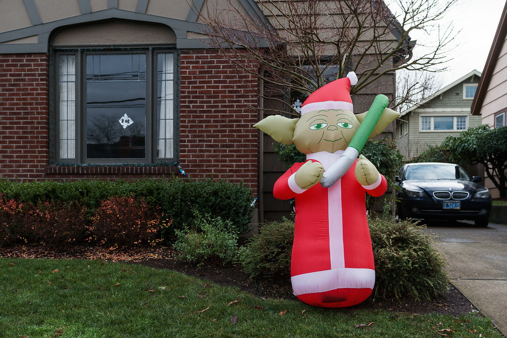 An inflatable yoda dressed as Santa Claus and holding a ligthsaber sits outside a house on a rainy winter day in the Irvington neighborhood of Portland, Oregon