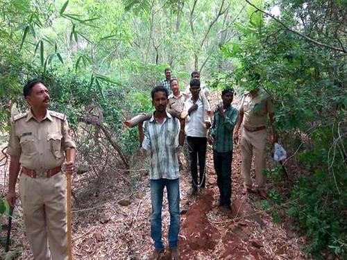 बंगलुरु में चंदन की लकड़ी काटने के आरोप में गिरफ्तार युवकों को ले जाती पुलिस