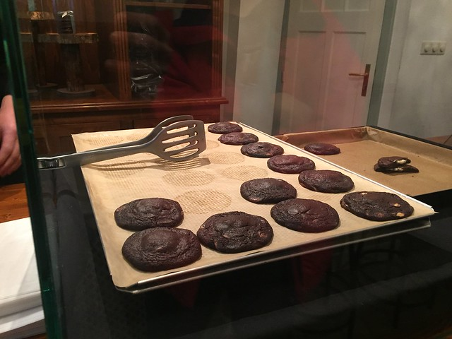 View of a bakery window - multiple large flat chocolate cookies cooling on baking sheets.