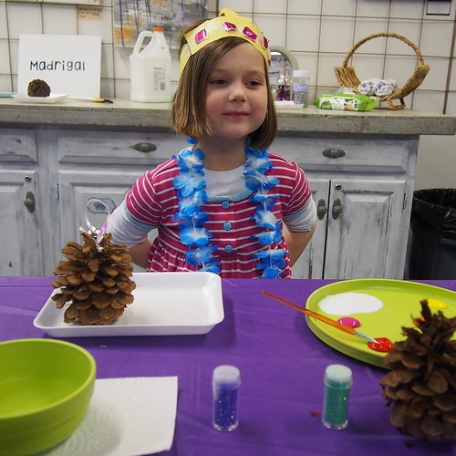 Madrigal's chosen birthday party activity: painting pinecones and adding glitter!