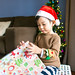 Portrait of a baby boy opening gift with a Christmas hat in Christmas morning