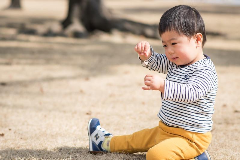 皇居外苑で芝生に座り遊ぶ子ども