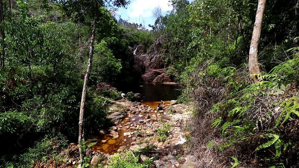 "Trek through secondary rainforest to the refreshing ""black pool"" waterfall"