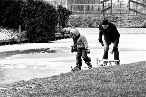 Opa leert kleindochter schaatsen.