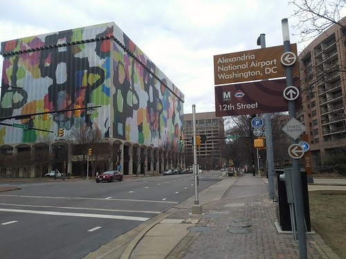Building wrapped with colorful treatment in Crystal City and Metrorail/VRE sign