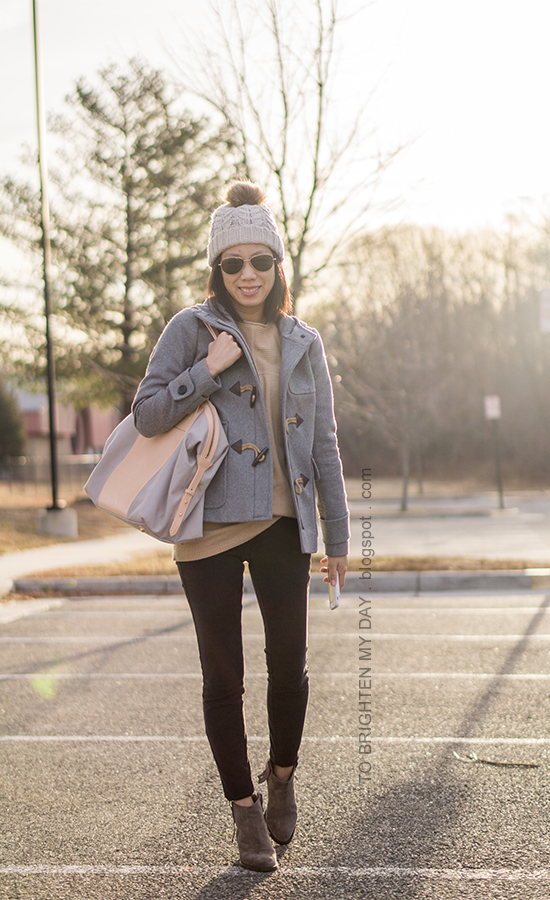 pom beanie, gray wool coat with toggles, camel sweater tunic, black jeans, gray suede ankle boots, beige and gray tote