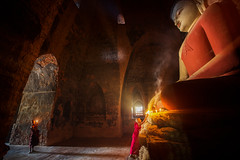 Monk in Bagan old town pray a buddha statue with candle