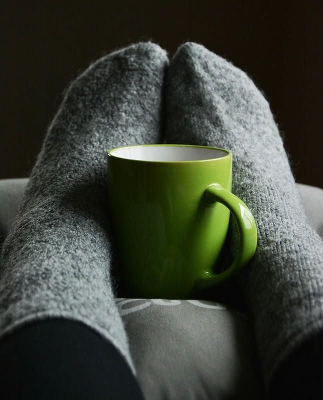 Close up of feet in fluffy grey socks with a green mug