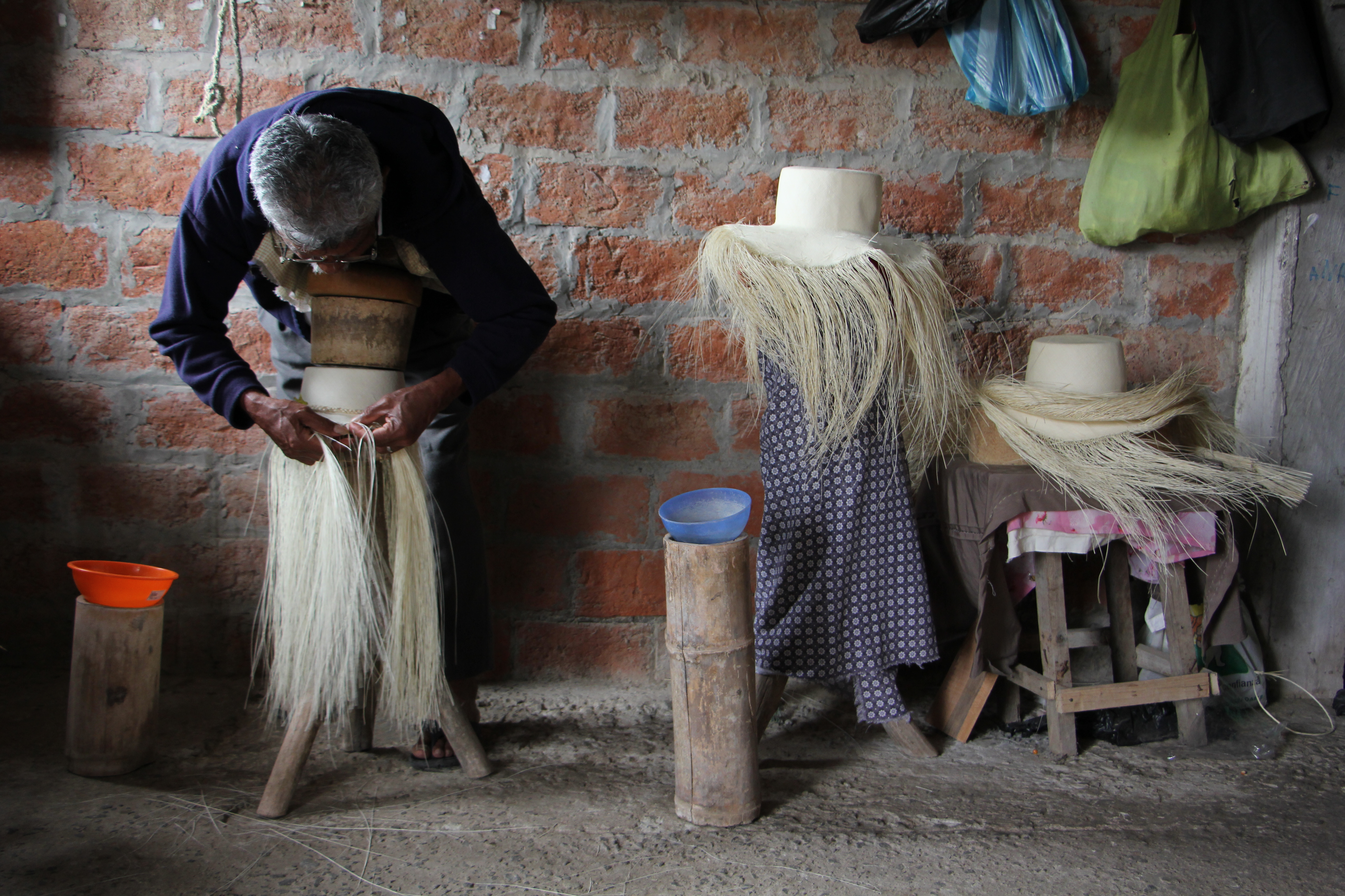 The toquilla straw hat is woven from fibres from a palm tree characteristic of the Ecuadorian coast. Cenovio is a master weaver, with over 70 years, every day of his life he acquires this pose. A grade 30 hat can be done by him in one month and a half, something that could take other weavers more than 2 months. Photo taken on August 5, 2016.