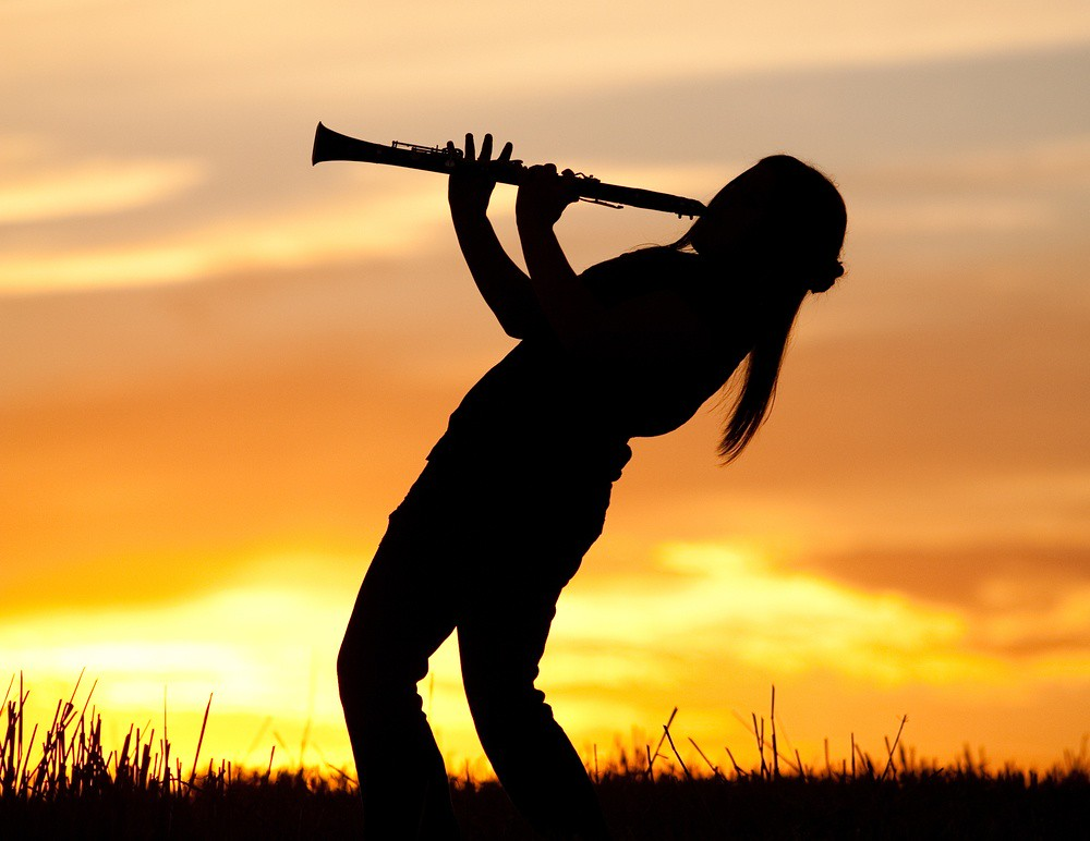woman enthusiastically playing clarinet outdoors