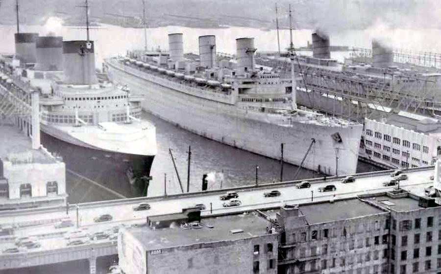 SS Normandie, RMS Queen Mary in her gray troopship colors, and RMS Queen Elizabeth still in her Cunard livery, moored in New York harbor, early 1940.