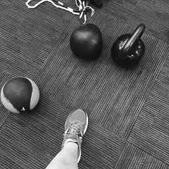 black and white photo of a kettle bell weight and two medicine balls, along with part of a human leg and sneaker-shod foot