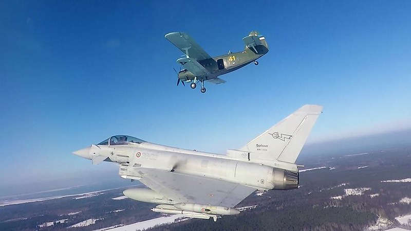 Italian Air Force Eurofighter Typhoon is flying near an Eesti õhuvägi Estonian Air Force An-2 biplane aircraft.
