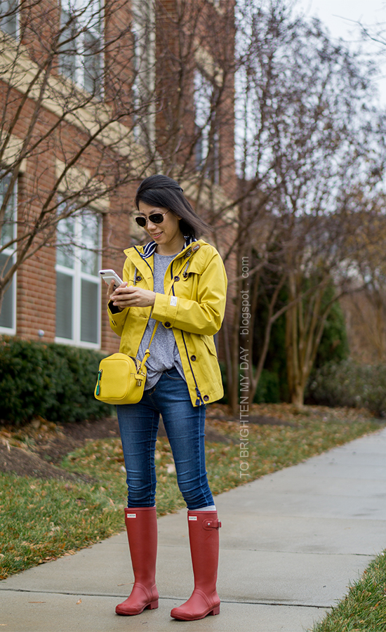 yellow rain coat, gray twist front top, yellow crossbody camera bag, skinny jeans, socks, red rain boots