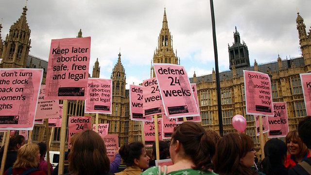 Women with placards protest Embriology Bill outside Westminter.