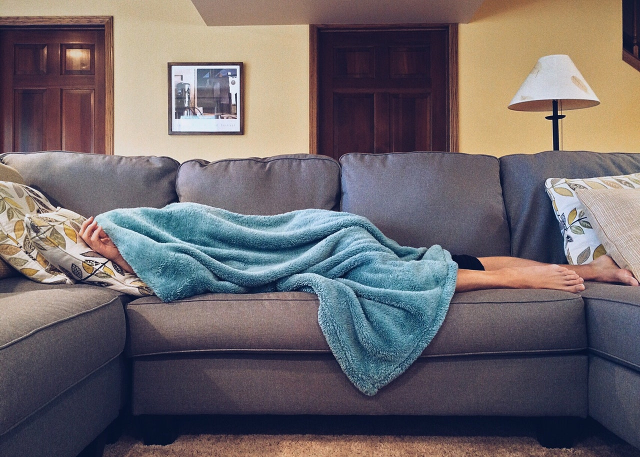 person laying on sofa covered in a blue blanket