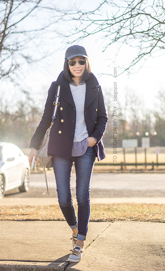 gray baseball cap, gray sweatshirt with ribbon ties, navy striped button up shirt, gray tote with striped strap, skinny jeans, navy pea coat, canvas sneakers