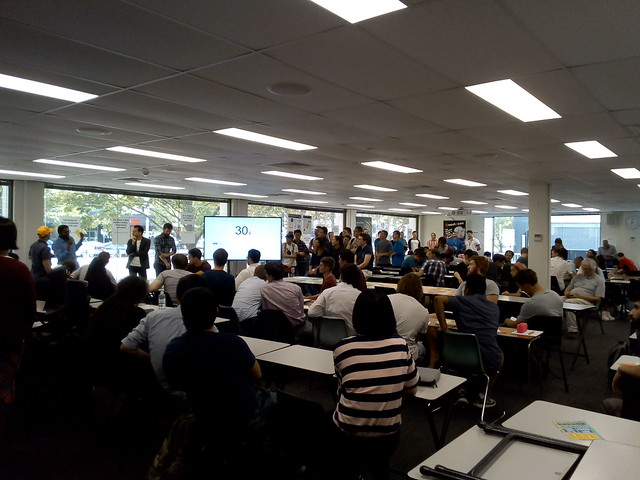 A flat floor large classroom at ANU, with large mobile LCD screens used to relay presentation to the back of the room.