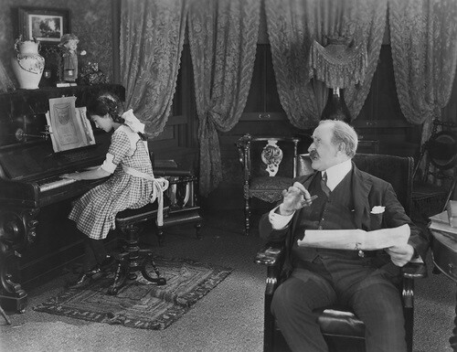 Antique image of formally dressed teacher instructing piano student