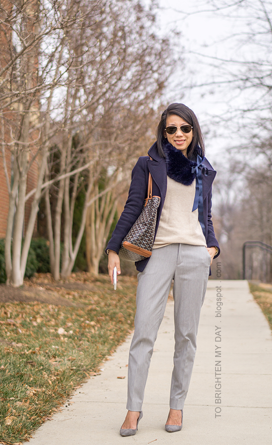 navy faux fur scarf with ribbon tie, navy pea coat, camel sweater, gold watch, gray pants, patterned tote, gray suede pumps