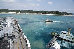 A tug boat guides USS Bonhomme Richard (LHD 6) away from the pier in Okinawa, Feb. 2. (U.S. Navy/MC2 William Sykes)