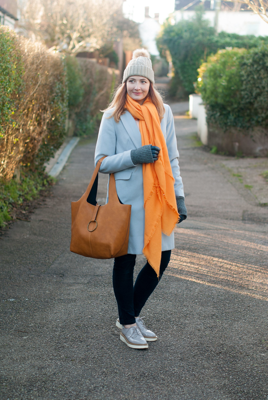 Bold brights winter style: Tangering orange scarf with pale grey duster coat, blue velvet trousers, grey flatforms and taupe pom pom beanie | Not Dressed As Lamb, over 40 style