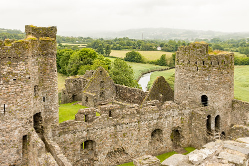 kidwelly castle carmarthenshire wales ruins fort tower stonework wall battlement landscape river field tree grass