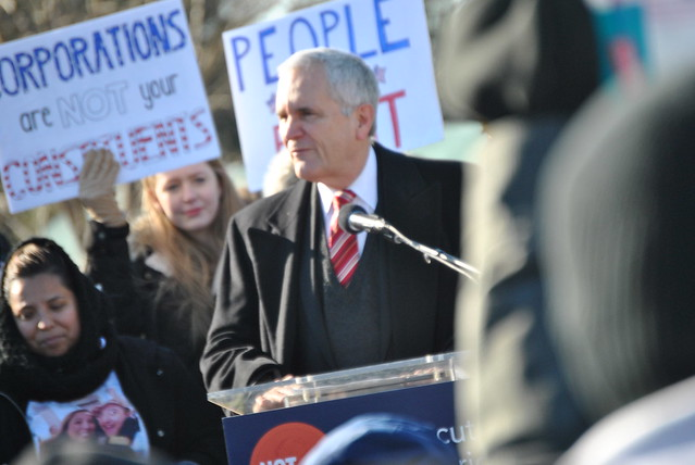 A man in a suit and tie speaks at a outdoor podium with protesters holding signs behind him