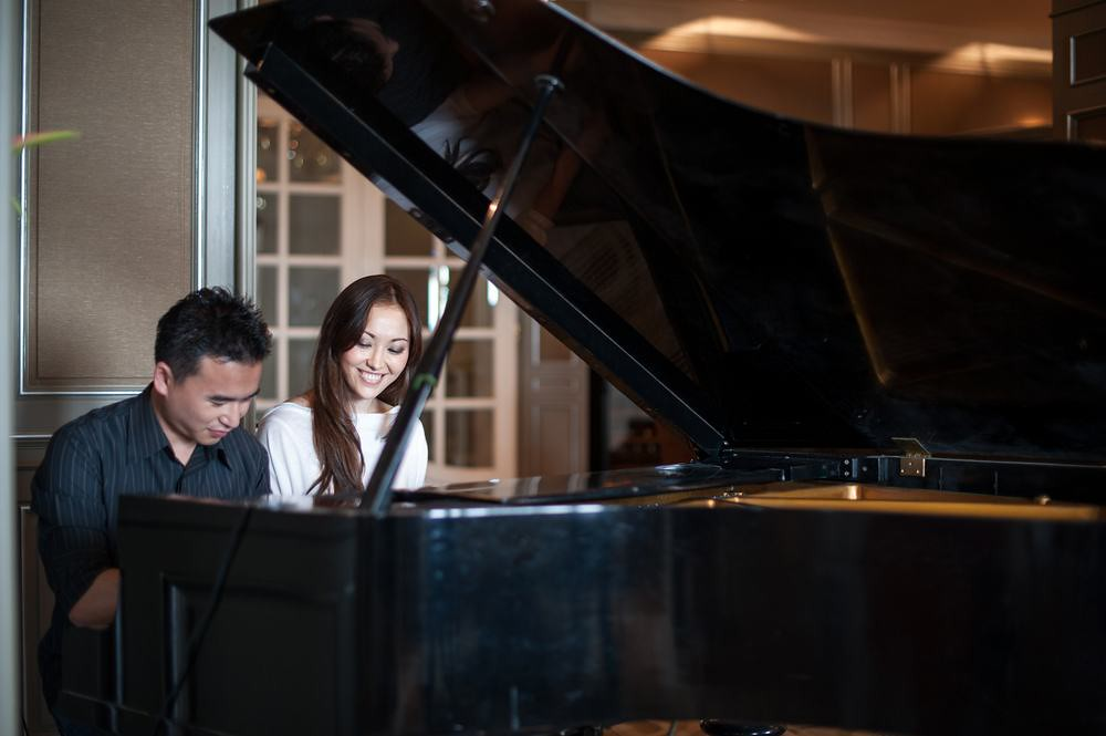 Asian couple playing piano