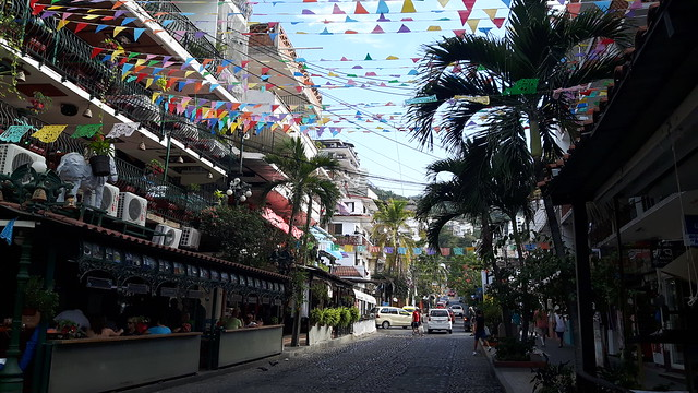 Cobblestone street with banners hanging between the buildings in Puerto Vallarta